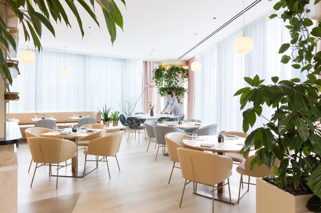 Foto do espaço para jantar, com mesas postas e poltronas vazias, no restaurante Botanist, do Fairmont Pacific Rim