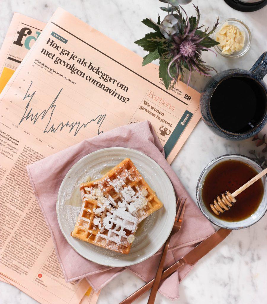 Foto de jornal com notícia sobre coronavírus em língua estrangeira, e waffles com açúcar e pode de mel ao lado