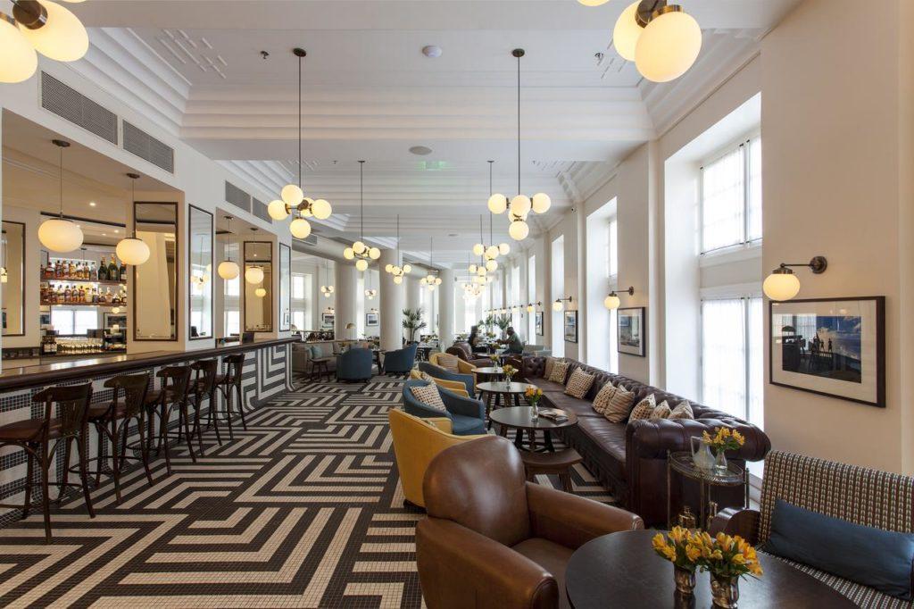 Área comum do hotel, onde se vê o bar com balcão e banquetas, e poltronas e sofás com mesinhas, além de carpete geométrico e lustres estilizados