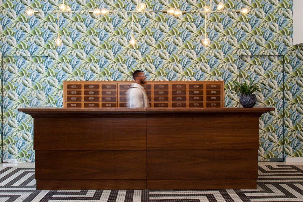 Foto da recepção do hotel, com balcão de madeira, caixinhas numeradas, plantas, lustre, carpete geométrico e papel de parede floral, além de atendente em movimento