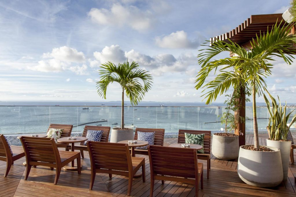Terraço do Fera Palace com cadeiras, mesinhas e palmeiras, além de vista direta para a Baía de Todos os Santos