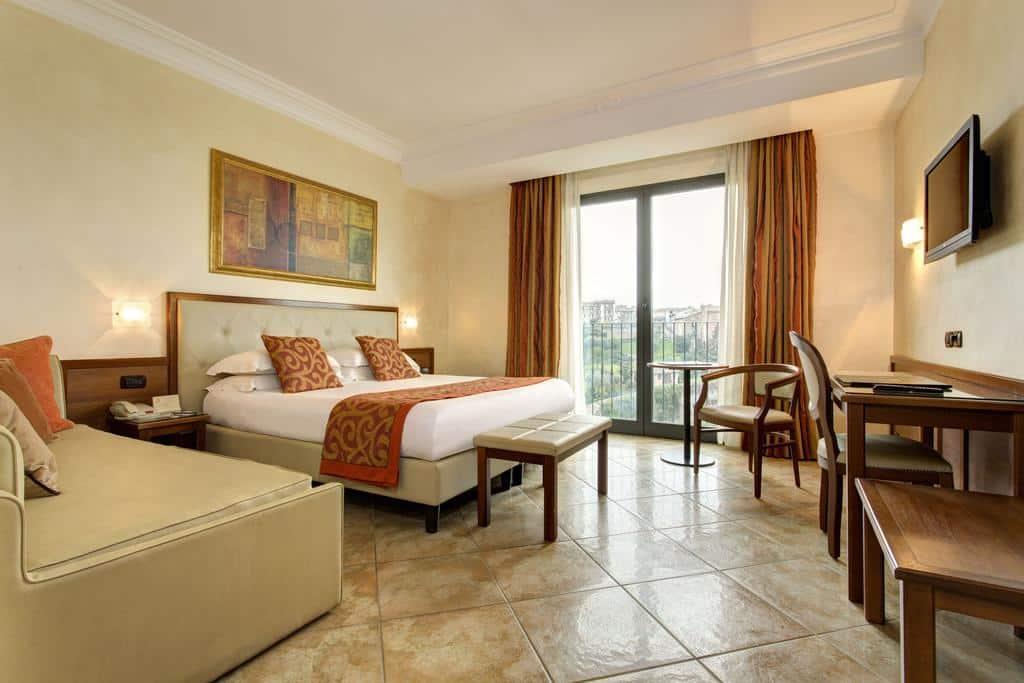 Quarto amplo com cama de casal, cortinas, quadro, mesa de trabalho e cadeiras no Hotel Athena, em Siena, uma das cidades para visitar numa lua de mel na Itália