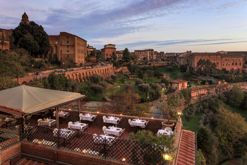 Foto aérea de terraço do Hotel Athena, com vista para parte arborizada da cidade de Siena, na Itália