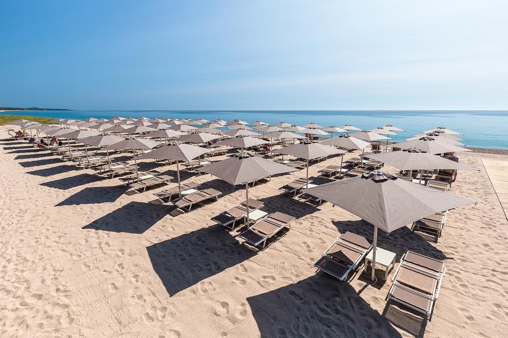 Praia privativa do Hotel Corte Bianca, com espreguiçadeiras e guarda-sóis vazios em dia de sol, um local perfeito para a lua de mel na Itália