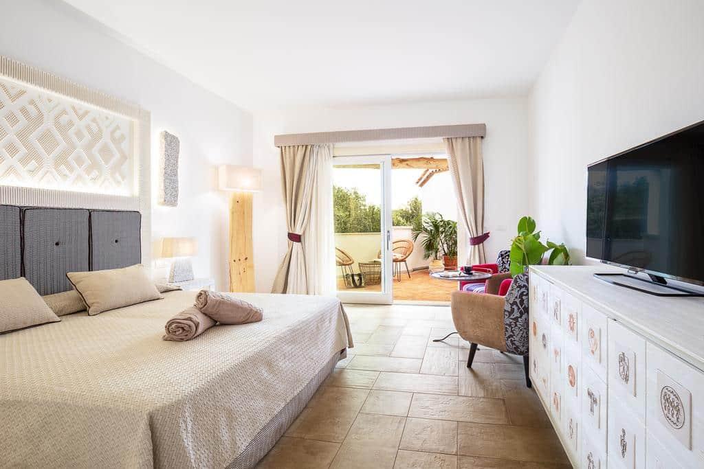 Foto do quarto espaçoso do Hotel Corte Bianca, com decoração clara e fina, perfeito para uma estadia de lua de mel na Itália