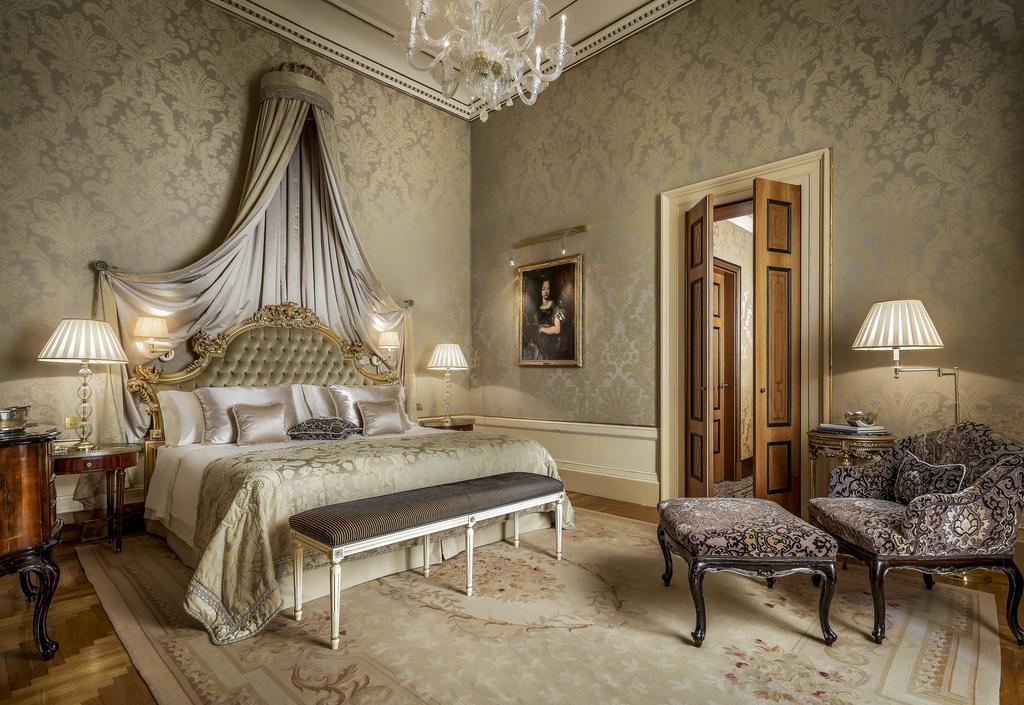 Quarto do Hotel Danieli, com móveis clássicos, como cama, poltrona, lustre e quadro, em ambiente requintado, perfeito para uma lua de mel na Itália