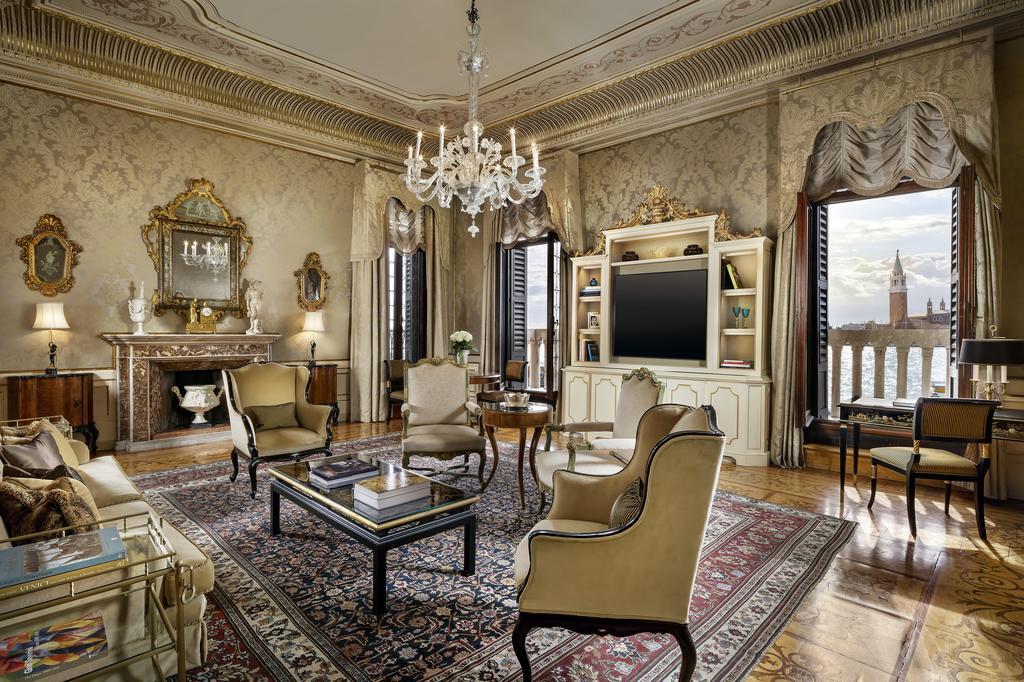 Sala de acomodação do Hotel Danieli com ambiente decorado em detalhes, com lareira, mesa, poltronas, estante, TV plana, sofá e vista para os canais de Veneza
