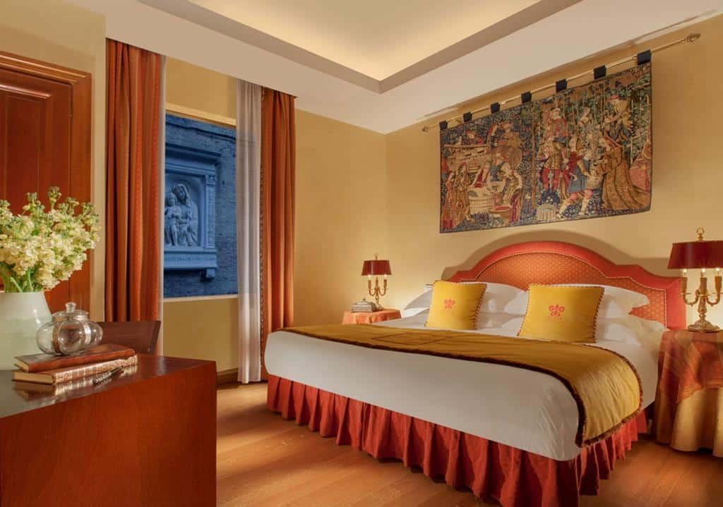 Quarto com cama ampla e tapeçaria de enfeite no Hotel Raphael, em Roma