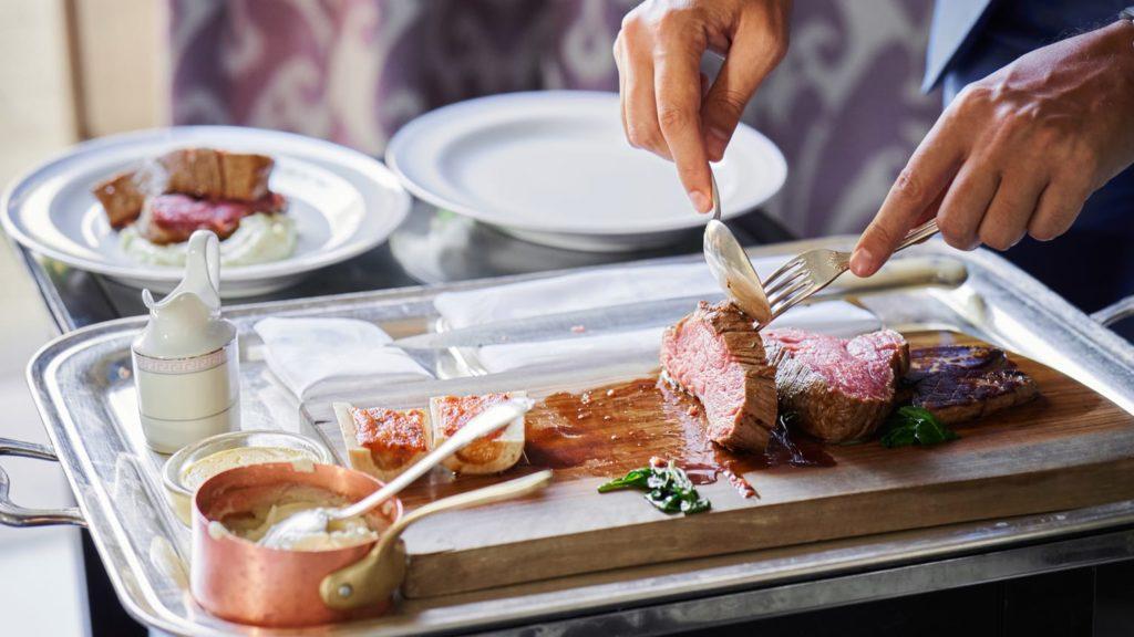 Mãos de pessoa cortanto carne mal passada em tábua, com dois pratos dispostos próximos, e panelinha com molho