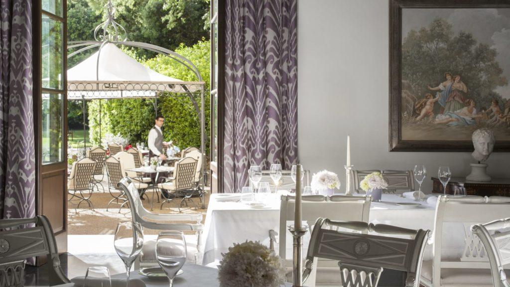 Ambiente interno do restaurante Il Palagio, com decoração clássica, e vista para a área externa com mesas e cadeiras sob cobertura ao lado de arbustos