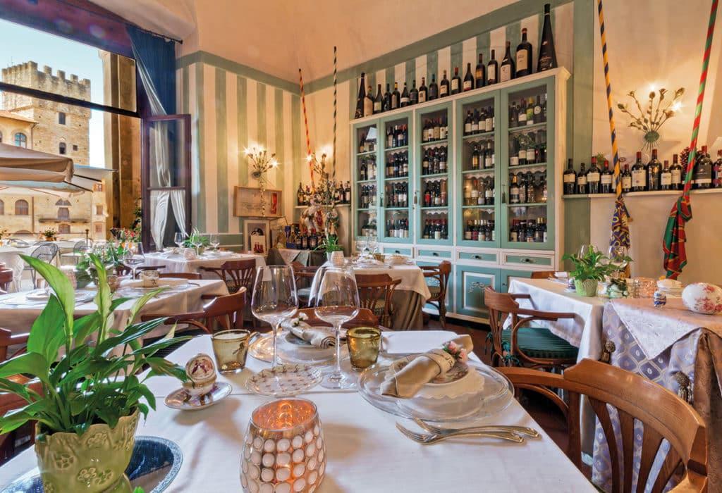 Ambiente interno do restaurante La Lancia d'Oro, com paredes listradas e armário cheio de garrafas de vinho completando a decoração