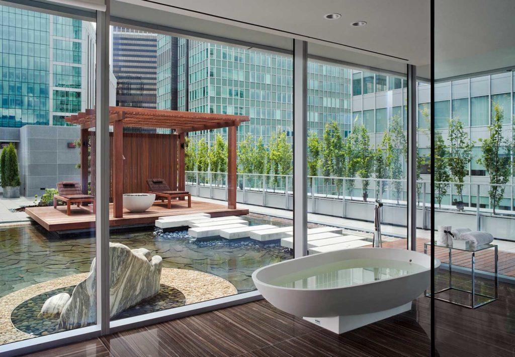 Foto da lagoa de meditação, gazebo com espreguiçadeiras, caminho de pedras e banheira, além das paredes de vidro