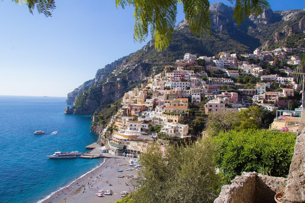 Foto da Costa Amalfitana, com casinhas na beira do morro, mar azul turquesa, pessoas na paraia, e barcos parados no mar