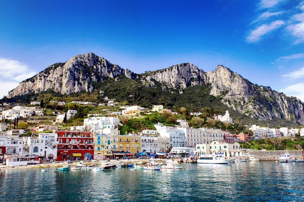 Foto de costa da Ilha de Capri, com casinhas coloridas e grande cadeia de montanhas ao fundo