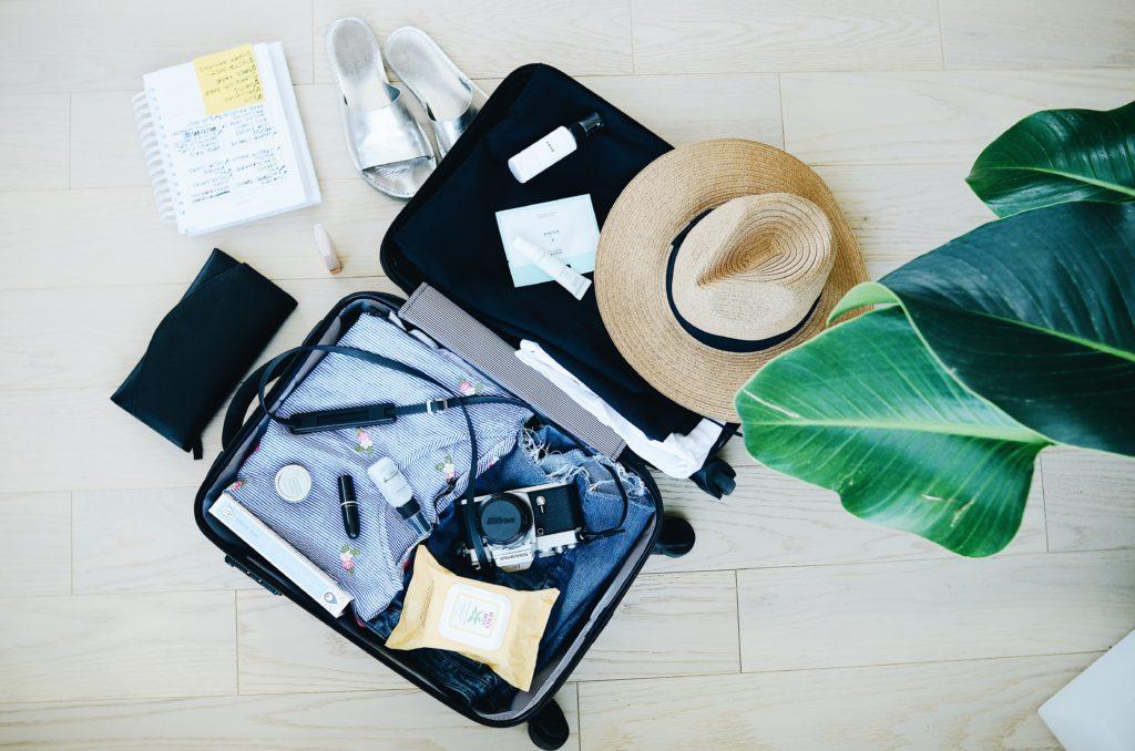 Foto de mala de viagem com roupas, maquiagem, chapéu, câmera fotográfica e outros itens para lua de mel na Itália