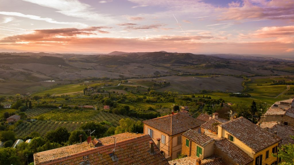 Foto de casas rústicas e plantações em colinas na Toscana, um dos destinos para lua de mel na Itália