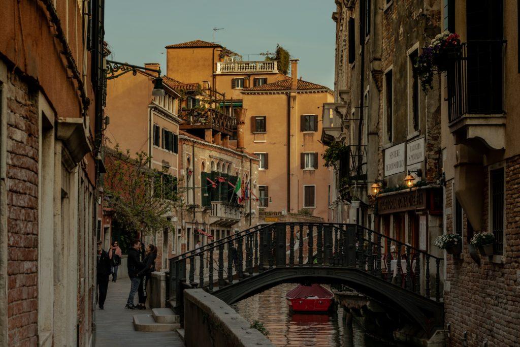 Ruela em Veneza, com ponte ligando a calçada aos prédios do outro lado do canal, e casal conversando próximo em clima romântico, como em uma lua de mel na Itália