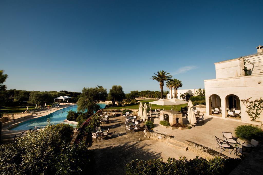 Foto da área comum do hotel Masseria San Domenico, um dos indicados para lua de mel na Itália, com piscina, mesas, cadeiras e guarda-sóis