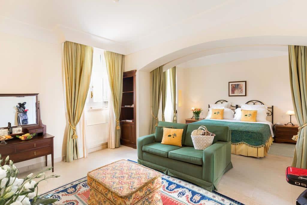 Foto de quarto do hotel Masseria San Domenico, com sofá e lençol verde, cortinas oliva, almofadas amarelas, pufe e tapete