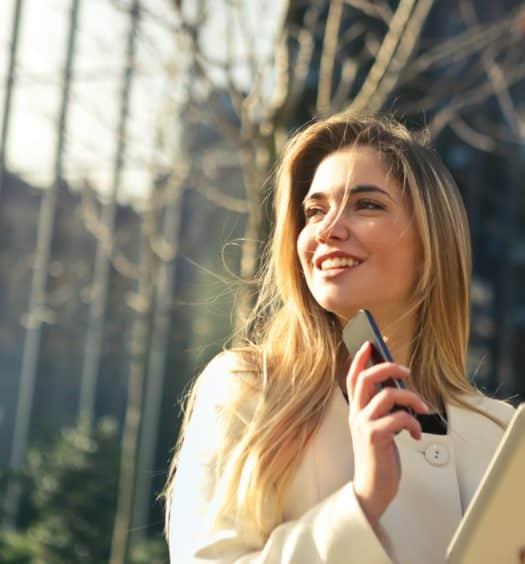 mulher segurando celular e tablet na cidade representando se a America Chip é bom