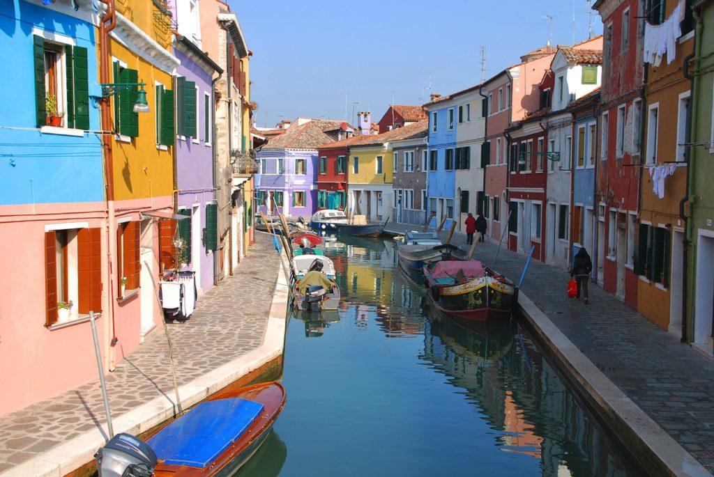 Casinhas coloridas de Murano, com canal cortando a rua e barcos parados na água, sendo um dos passeios indicados para a lua de mel na Itália