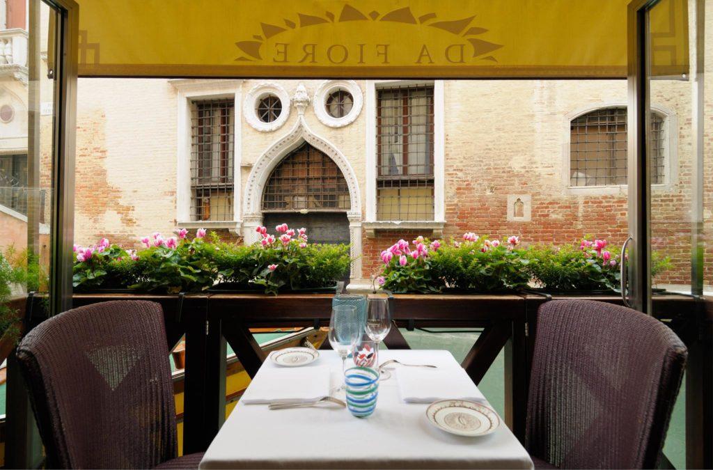 Mesa para dois no restaurante Osteria da Fiore com vista para os canais de Veneza com barcos, uma indicação de onde comer durante lua de mel na Itália