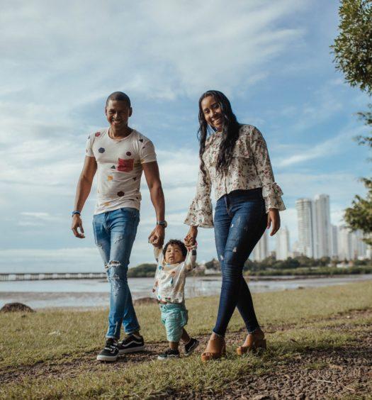pai e mae caminhando junto com seu filho pequeno