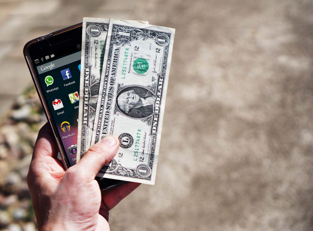 mão segurando dólares americanos e um celular smartphone