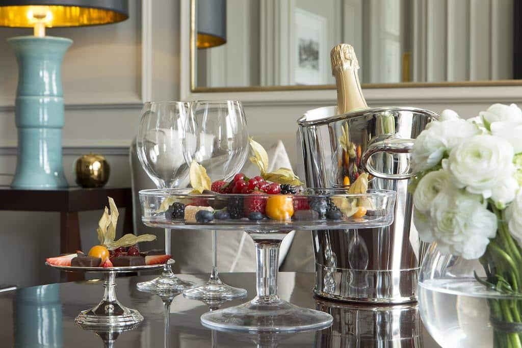 Foto de detalhe do quarto no Portrait Firenze, com garrafa de champanhe, taças, frutas, flores e chocolates