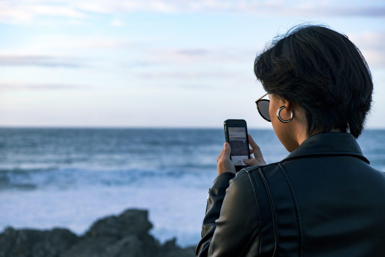 mulher fotografando com smartphone a praia do guincho em portugal