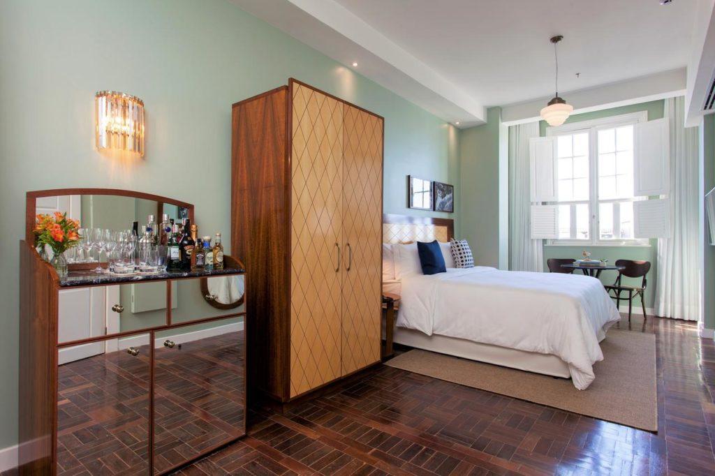 Quarto amplo com paredes verdes, cama de casal, armário, cômoda e mesa com duas cadeiras