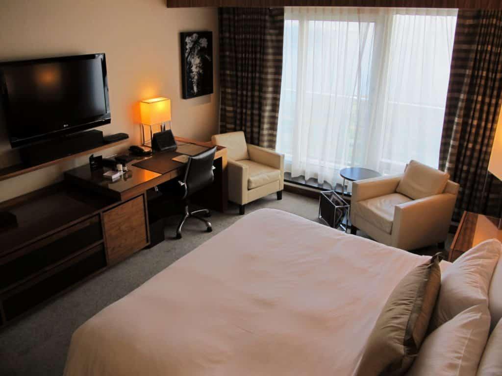 Foto do quarto do Fairmont Pacific Rim com cama de casal, mesa de trabalho, TV placa, poltrona e cortina