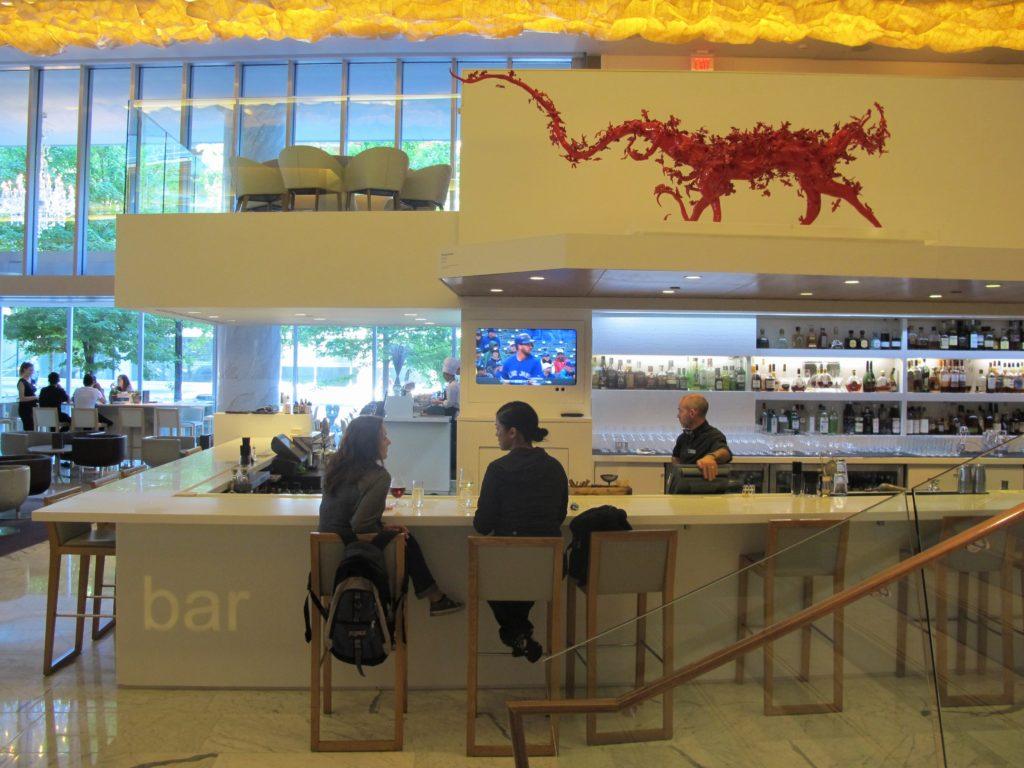 Foto do espaço de balcão do RawBar, com duas mulheres nas banquetas, um funcionário do local, uma TV e uma escultura vermelha sobre o bar