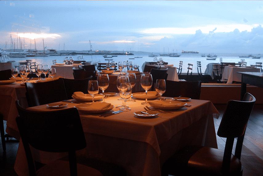 Mesas postas com pratos, talheres e taças no restaurante Amado, em Salvador, com vista direta para a marina