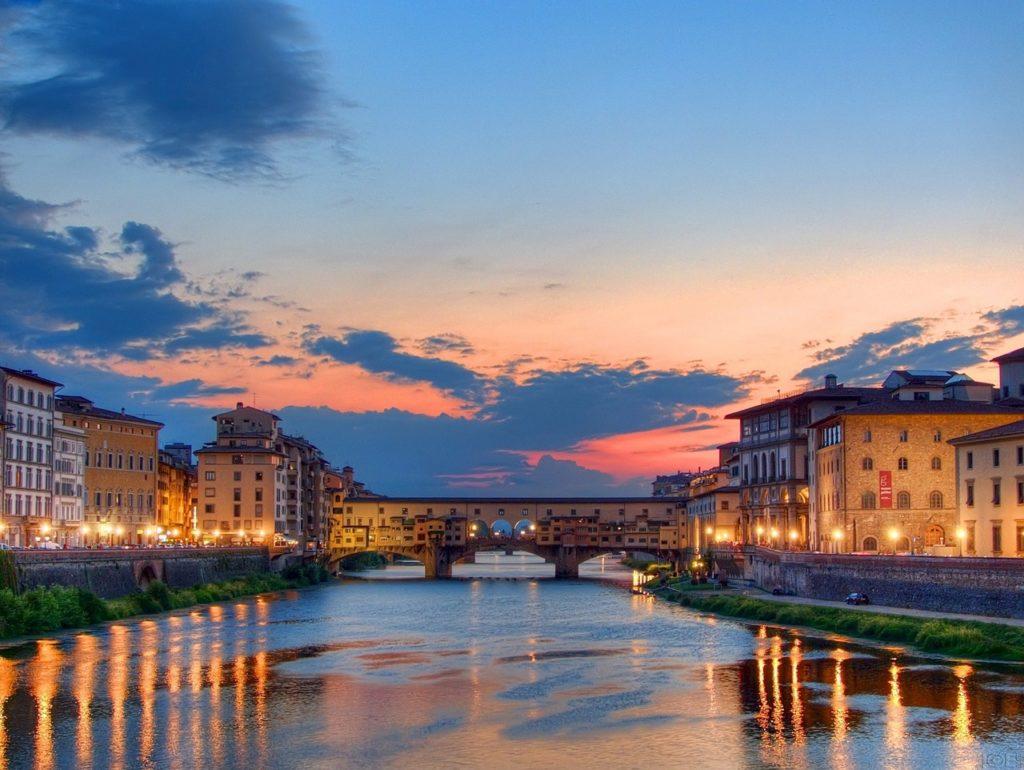 Foto do Rio Arno, em Florença, durante o pôr do sol, um dos passeios mais românticos para fazer durante uma lua de mel na Itália