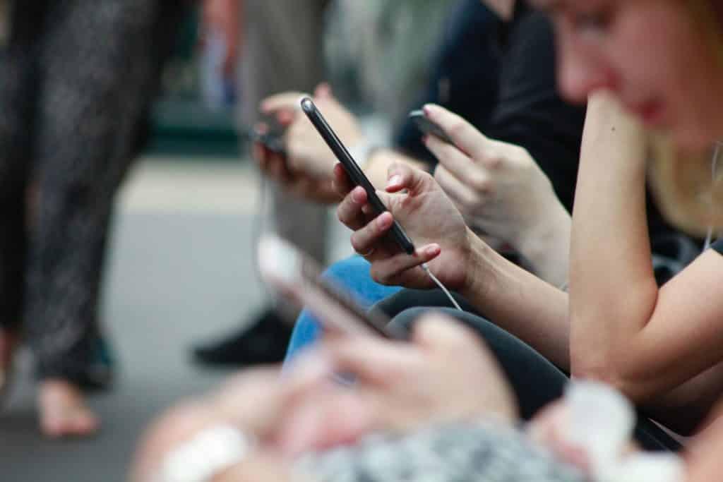 pessoas mexendo no celular procurando se a america chip é confiável
