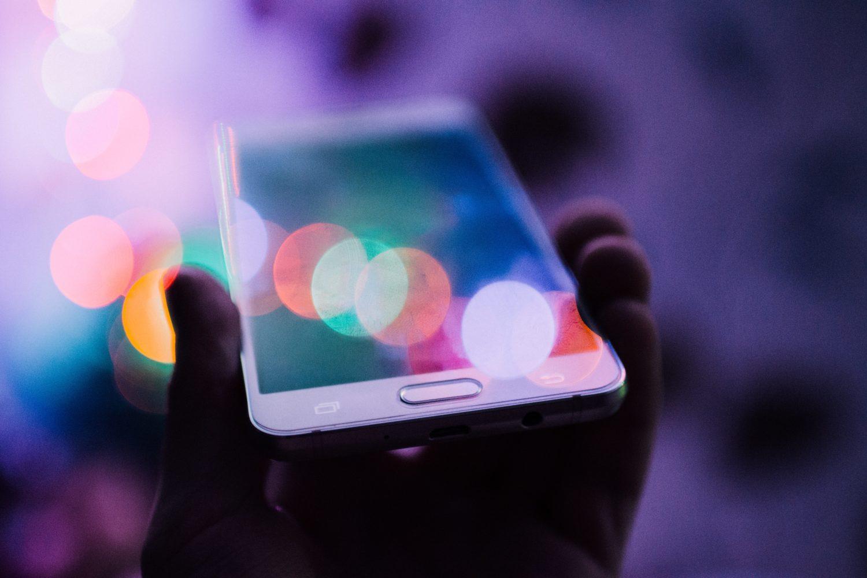 mão segurando um celular num ambiente escuro representando se a america chip é confiável