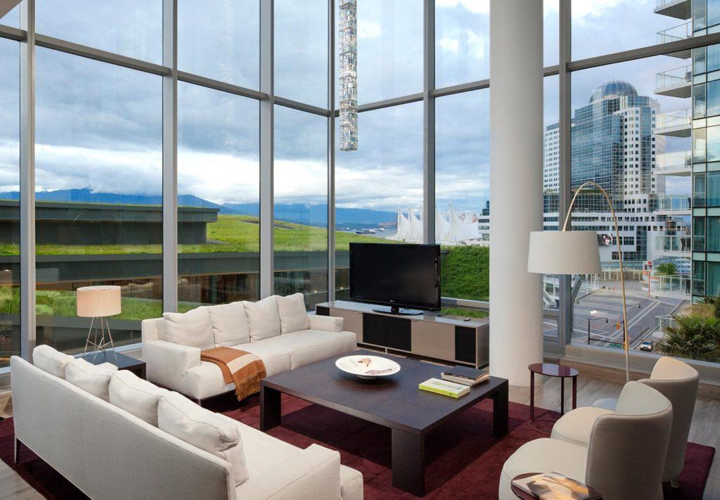 Foto da sala com sofá, poltronas e TV em frente às parede de vidro da Chairman's Suite, no Fairmont Pacific Rim