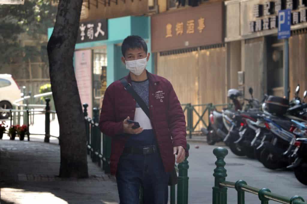 Pessoa caminhando em rua de cidade da China, usando máscara cirúrgica para tapar a boca e o nariz