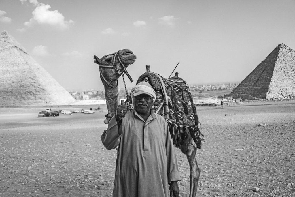 homem egípcio e seu camelo perto das pirâmides