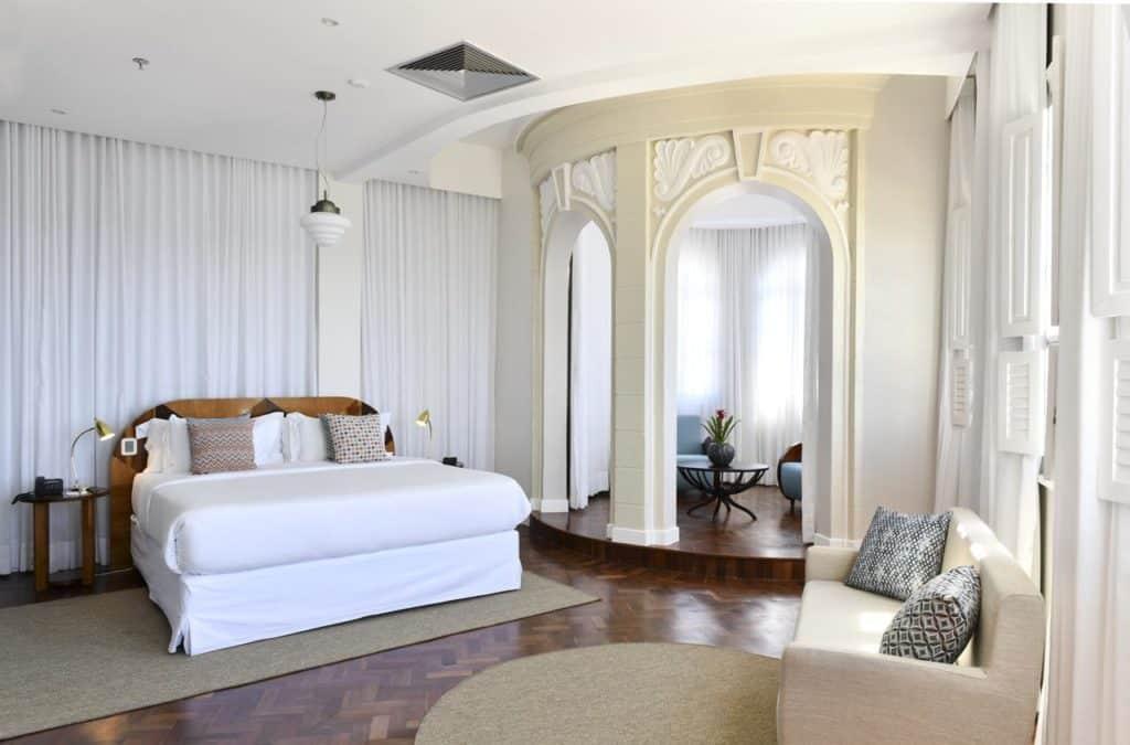 Suíte Presidencial do Fera Palace Hotel com cama ampla, sofá, almofadas e espaço arredondado com poltronas e mesinha