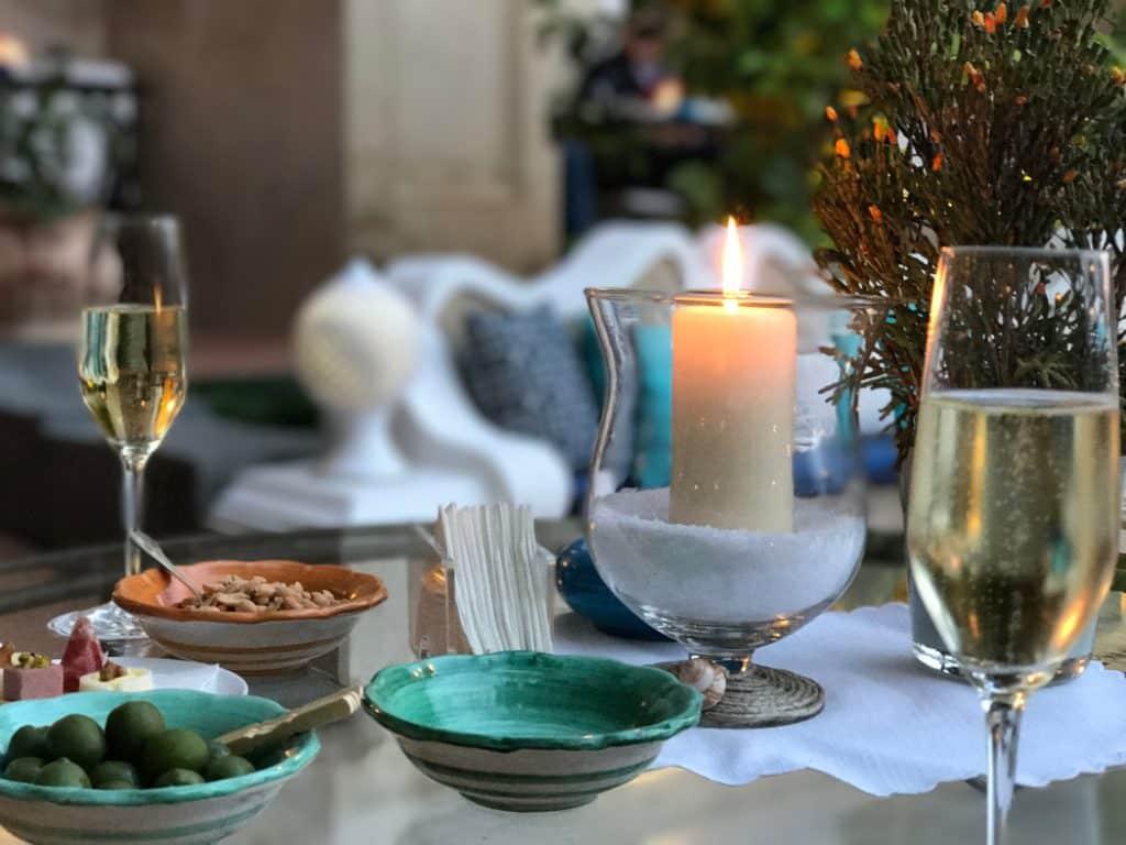 Foto de mesa com vela acesa, duas taças de champanhe, e tigelinhas com petiscos como azeitonas, amendoim, queijo, uma sugestão de surpresa para uma viagem de lua de mel na Itália