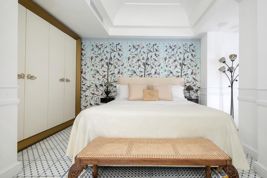 Cama de casal em quarto do Luxury Villa Excelsior Parco, com parede com pintura de passarinhos e grande armário