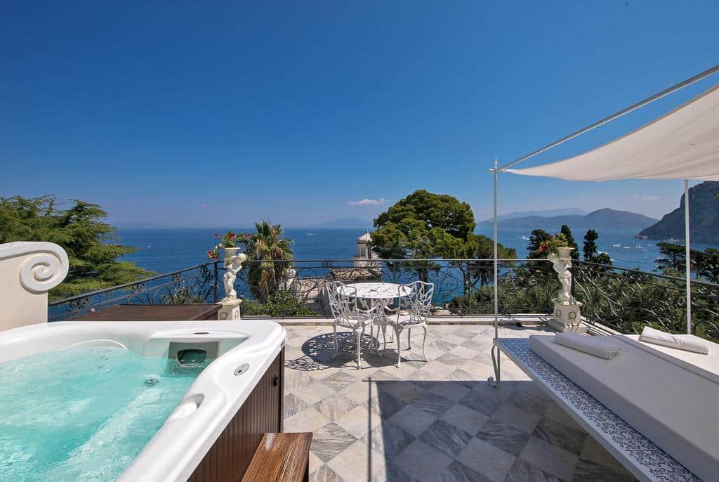 Hidromassagem, mesa com duas cadeiras e lona cobrindo duas camas de massagem no terraço do hotel Luxury Villa Excelsior Parco, na Sardenha