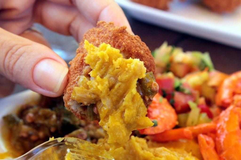 Mão segurando acarajé