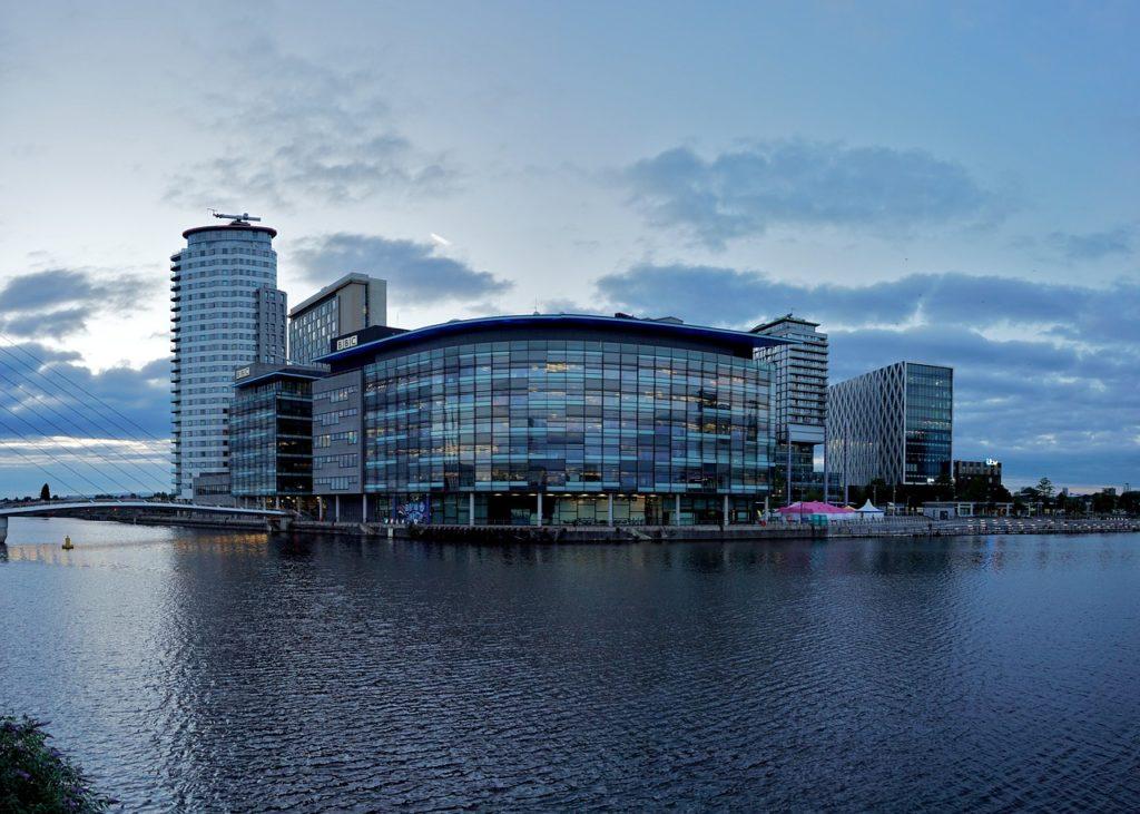 Área com grande construção e lago em Manchester