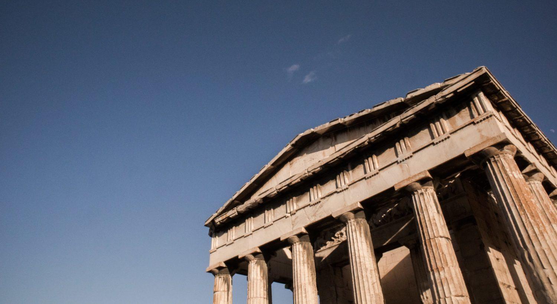 Atenas, na Grécia, com céu limpo e monumento antigo em primeiro plano