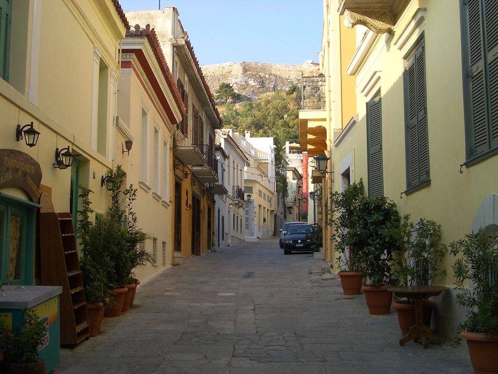 Rua estreita com carros estacionados e casinhas coloridas no bairro Plaka, em Atenas