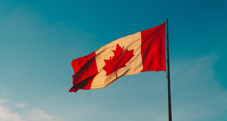 Bandeira do Canadá hasteada com céu azul ao fundo