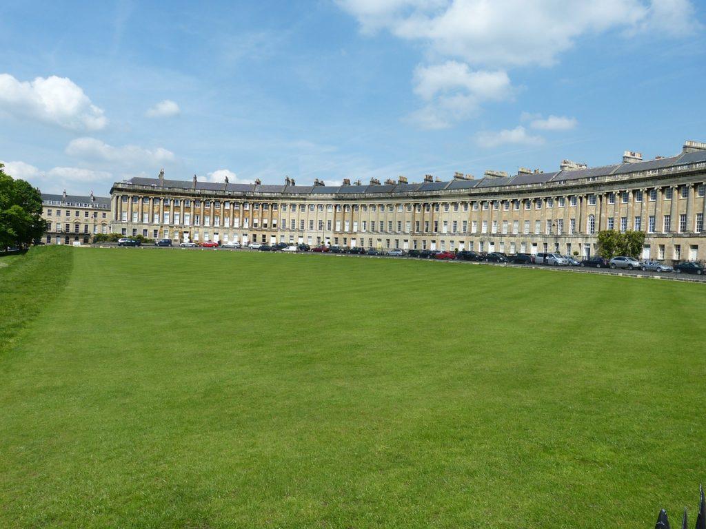 Campo com grama baixa e as casinhas do Royal Crescente, parte de Bath, ao fundo
